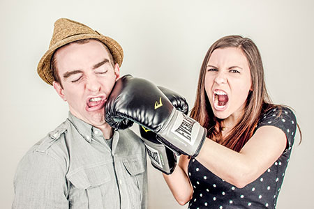 Girl with boxing gloves punches guy