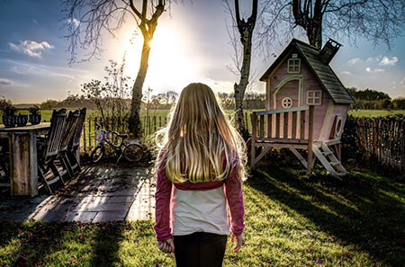 girl looking at sunset and cubby house